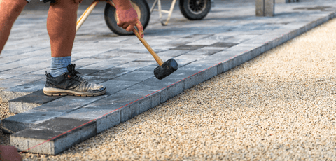 A contractor installing interlocking pavers on a driveway