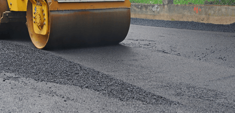 Rolling a freshly laid asphalt driveway to compact it