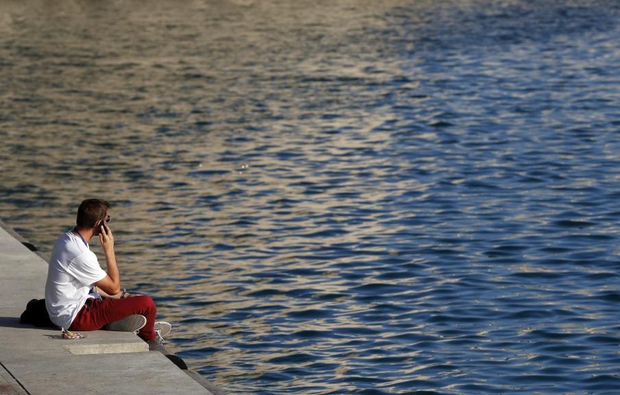 HOR116 - MARSELLA (FRANCIA), 1/7/2015.- Un hombre habla por teléfono hoy, miércoles 1 de julio de 2015, sentado frente a una playa del Mediterraneo en Marsella (Francia). La Agencia Nacional Metereológica Francesa (METEO FRANCE) anunció la llegada de una ola de calor en Francia en los días que vienen. EFE/ GUILLAUME HORCAJUELO