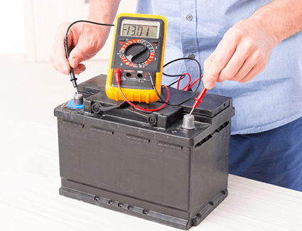 A man performs a test on this battery to determine its health and longevity