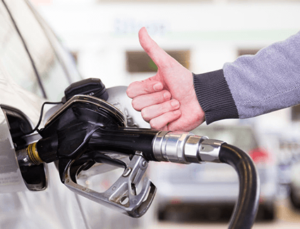 A person filling up their car and giving a thumbs-up sign.