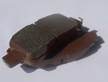 The friction material shown on this brake pad will wear down over time, until the pad needs to be replaced