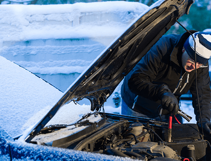 A man braves the snowy weather to jump start his car. Get your battery tested so you don't wind up jumping your car in the cold