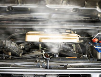 Steam billows out from the radiator of an overheating engine.