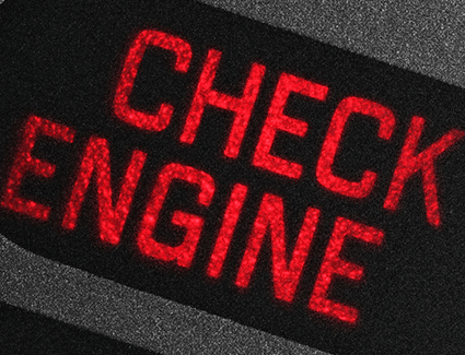Closeup of check engine light spelled out in red.