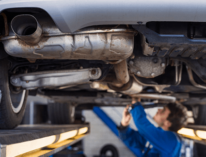 A technician inspects a vehicle's exhaust system.