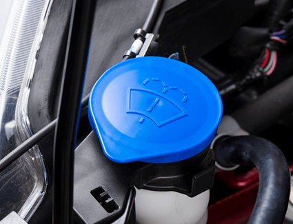 The wiper fluid cap, with its signature windshield wiper fluid symbol.
