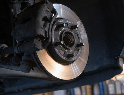A close-up view of a car with the wheel removed to show the disc brake rotor & caliper