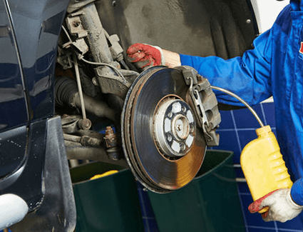 A technician bleeding the brakes in a vehicle.