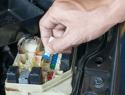 A technician installs a new fuse in this fuse box, complete with grey plastic relays.