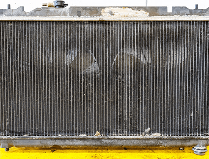 A car's radiator showing possible damage.