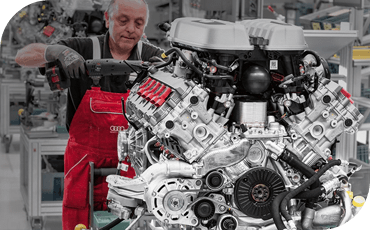 An engineer puts the finishing touches on this huge, powerful Audi V10 engine