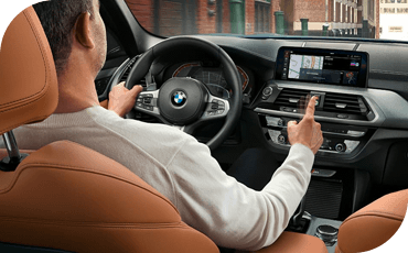 Person reaching for touchscreen in BMW X3