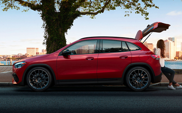 Red Mercedes-Benz GLA parked under a tree