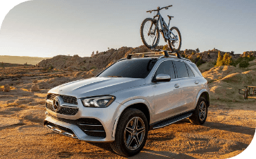 New Mercedes-Benz GLE off road with a bicycle mounted to the roof