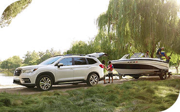 A 2019 Subaru Ascent towing a boat on a dirt road near a lake, with people standing outside the vehicle.