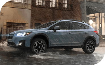 A 2019 Subaru Crosstrek drives down a wet street during a rainstorm, splashing water as it goes.
