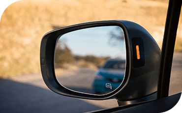 A close-up view of the side mirror on a 2019 Subaru Crosstrek, with a Blind Spot warning light illuminated.