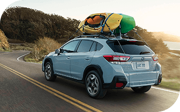 A rear 3/4 view of a 2019 Subaru Crosstrek driving down a winding road while carrying two kayaks on its roof rack.