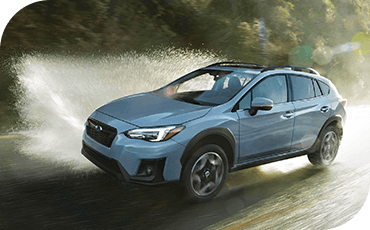 A 2019 Subaru Crosstrek drives down a rainy road, making a large splash as it goes.