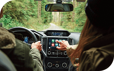 Two people are in a 2019 Subaru Crosstrek driving through a forest. The passenger is reaching for the touchscreen.