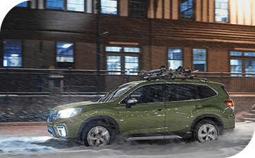 A 2019 Subaru Forester drives down a snowy downtown street.