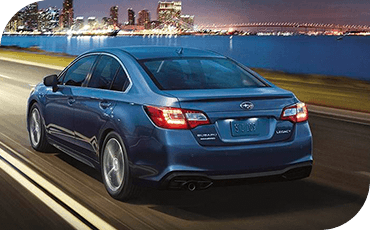 A rear 3/4 view of a 2019 Subaru Legacy driving down a road at night, with the lights of a city visible in the background.