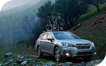 A 2019 Subaru Outback driving on a trail in the fog, with advanced headlight technology demonstrated.