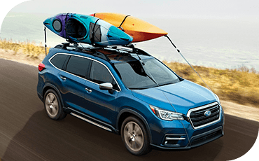 Subaru Ascent with kayaks on its roof driving down a coastal road