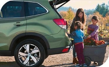 A family standing by a Subaru Forester