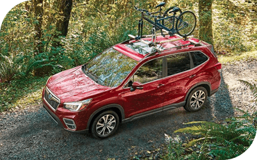 A 2020 Subaru Forester drives along a forested off-road trail