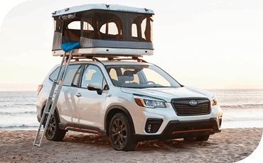 A 2020 Subaru Forester parked on a beach, with a tent accessory on the roof.
