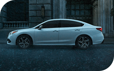 Subaru Legacy driving on rainy street