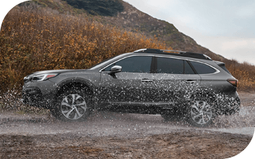 A 2020 Subaru Outback crossing a stream in an off-road trail.