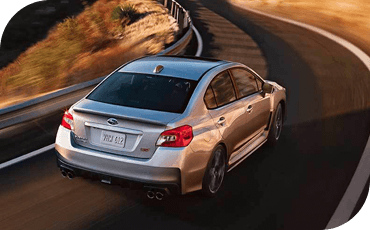 A 2020 Subaru WRX drives around a corner.