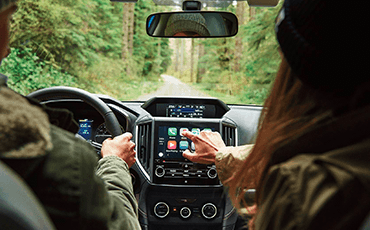A passenger in a Subaru Forester reaches toward the audio system touchscreen controls.