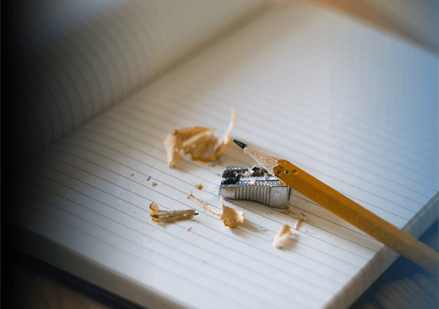 A pencil with sharpener and shavings on top of a lined pad of paper