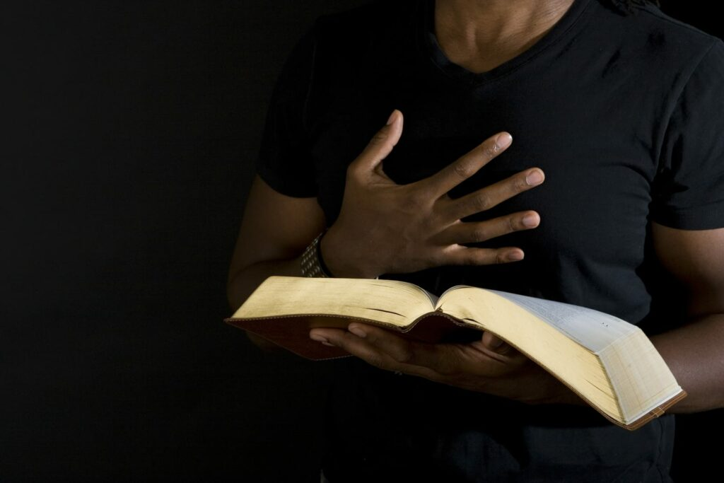 man holding Bible with hand on chest