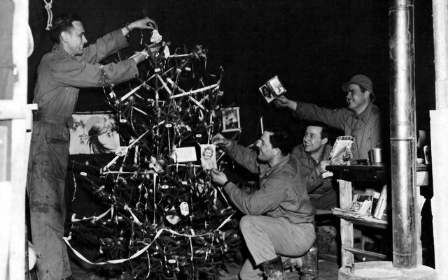 These GIs, attached to the 9th service command somewhere in England, take time out on Christmas Eve to decorate a tree at their base. They are, left to right: Pvt. George Rutter of Greenburg, Pa., Cpl. Conrad Myers of Fort Thomas, Ky., Cpl. Merrill Dunn of Laurel, Delaware, and Pfc. Edward Arnzen of Newport, Ky. 24 December 1943.