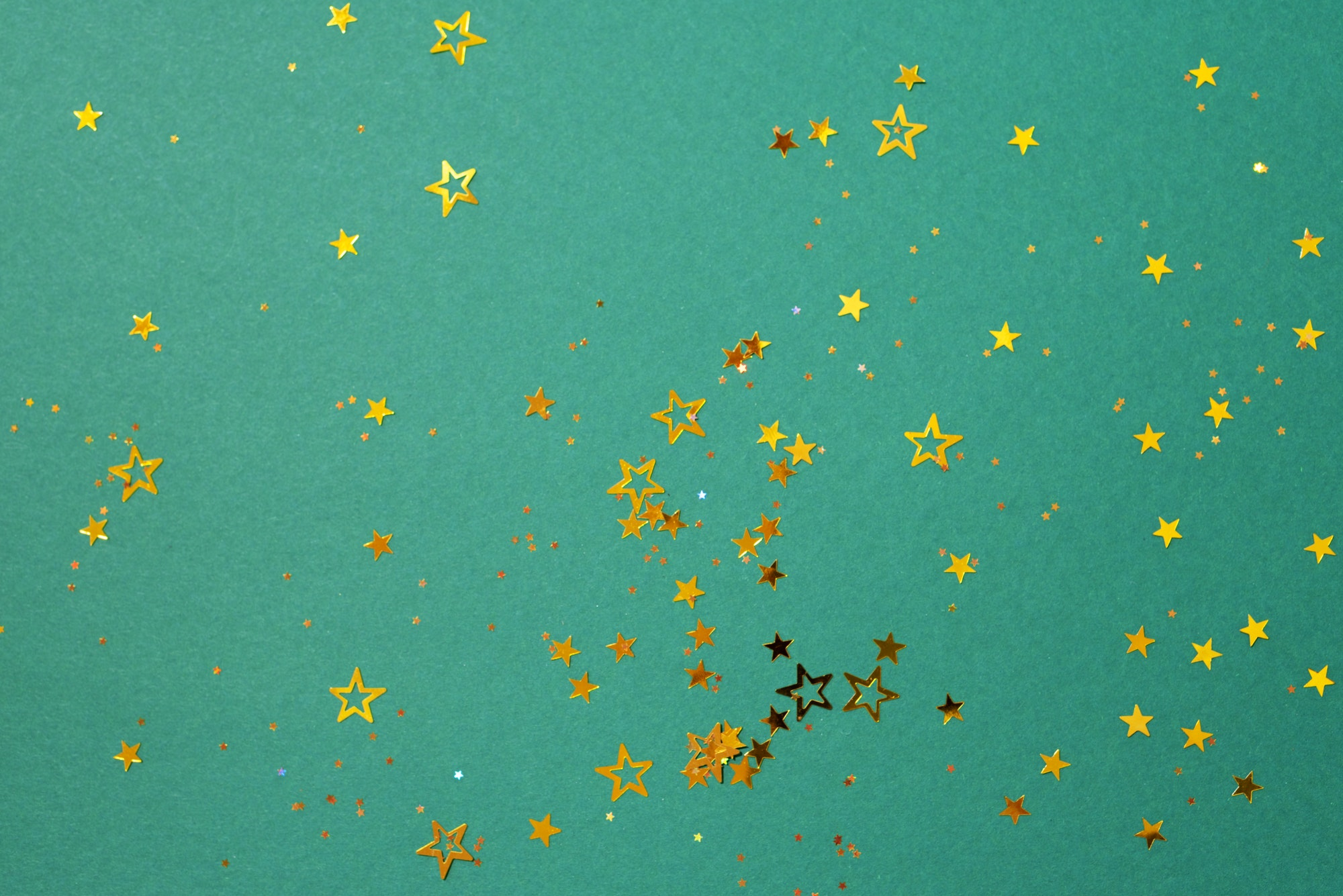 Golden star sparkles on green background