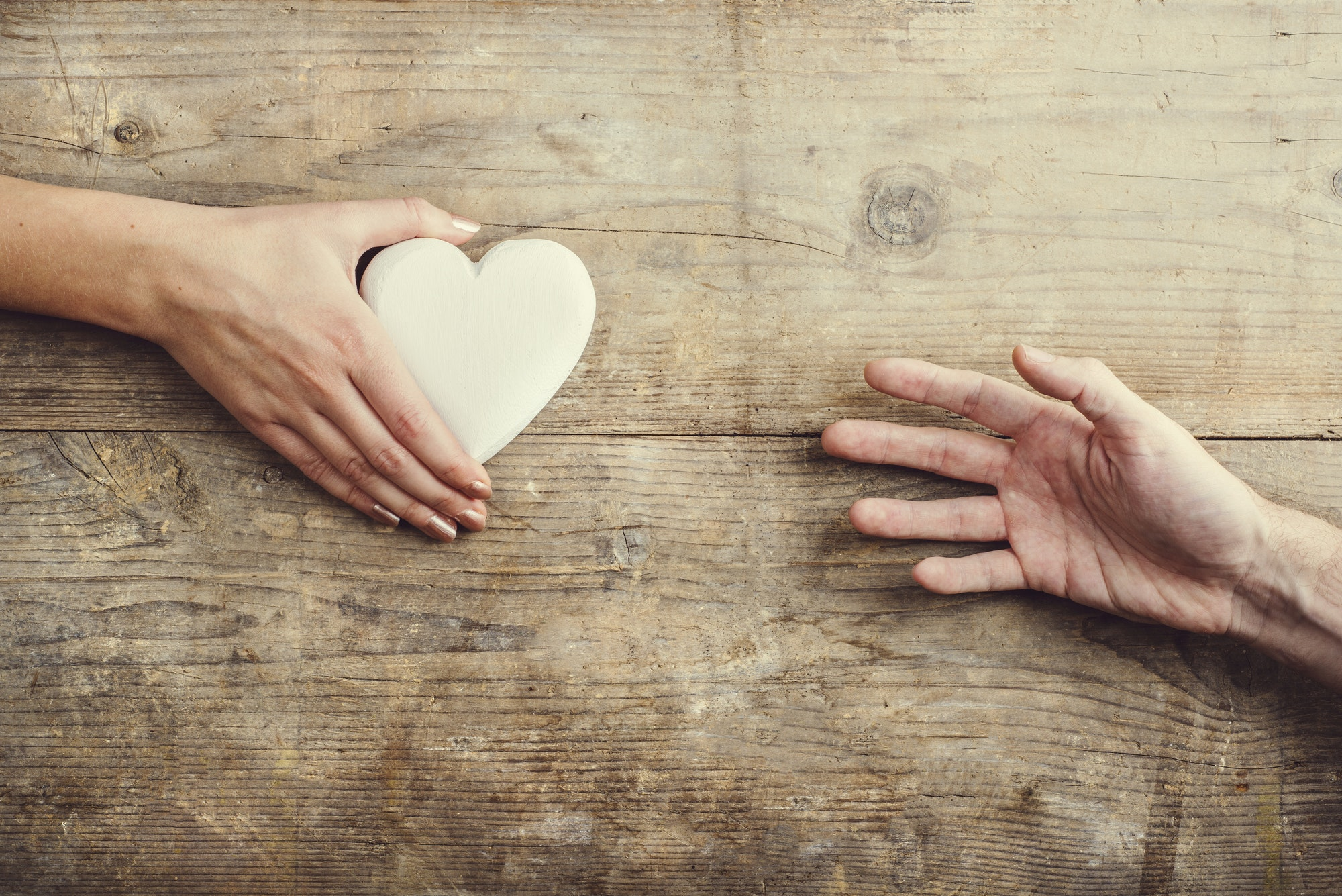 Man reaching for a heart to woman.