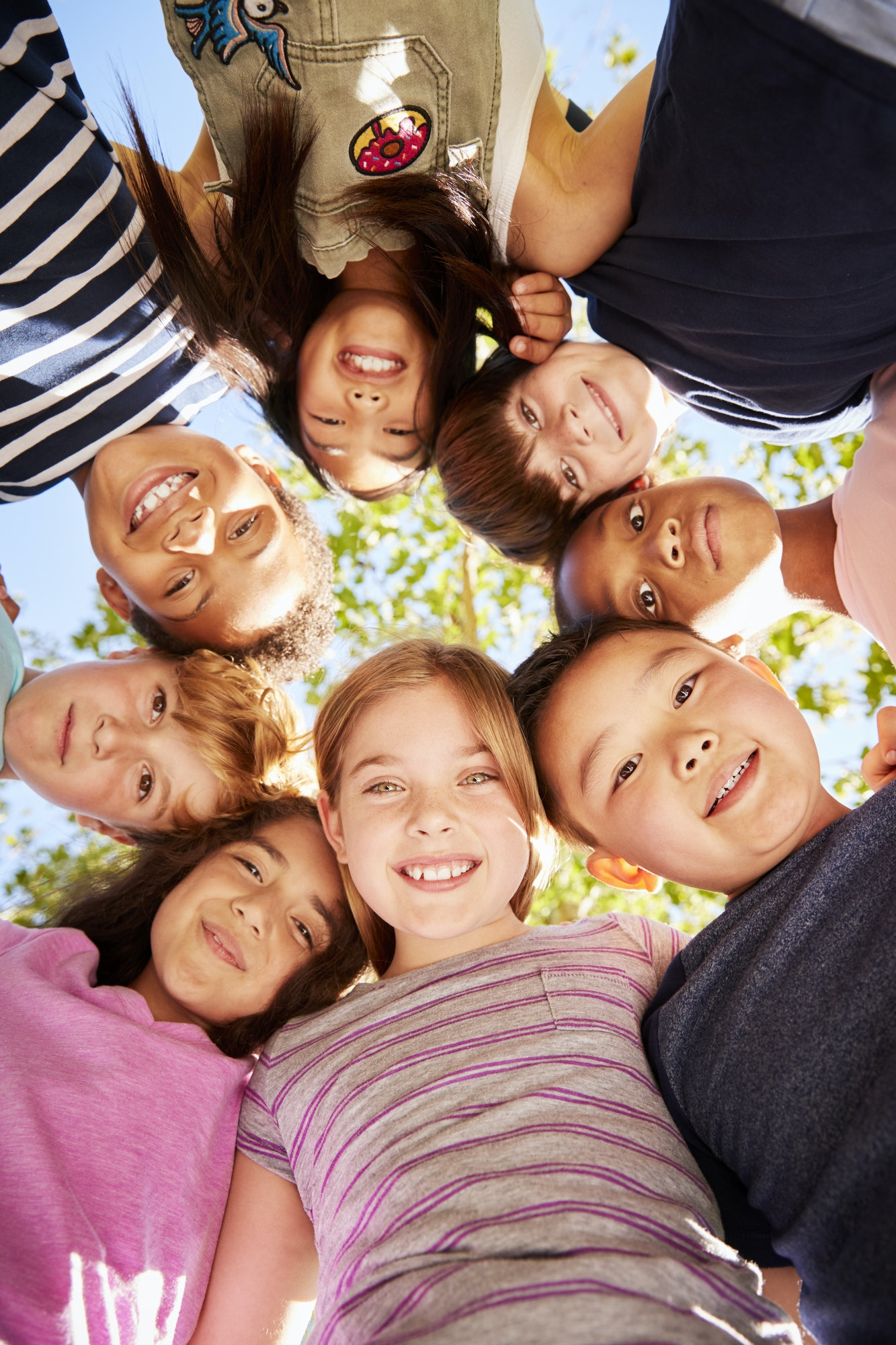 Group of kids outdoors looking down at camera,verticle