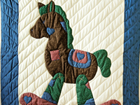 Navy and Multicolor Rocking Horse Crib Quilt