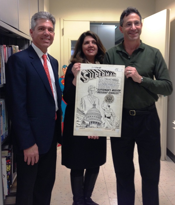 """Pictured from left: Al Plastino Jr. and MaryAnn Plastino-Charles holding the splash page of the original Superman art from """"Superman's Mission for President Kennedy"""" with Jay Kogan from DC Entertainment."""