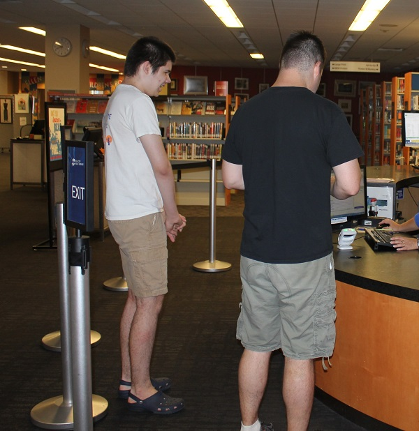 Teens checking out books at ICPL's Autism Accessible Browsing Hour