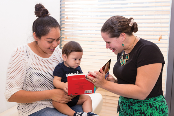 Aristy reads aloud to a young Bellevue patient. Photo by Spencer Sheldon