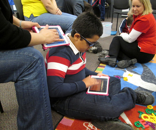 Program participant Fernando using an app to play music at Sensory Schoolage Fun.