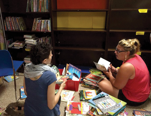In Baltimore, Patricia Rickle (left) and Julia Malanka, volunteers with UFPIA, sort books at the the new Wolfe Street Academy reading area. Courtesy of Mollie Fein