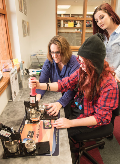 Jensen (left) with students using the button maker.