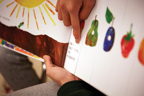 A student reads Eric Carle's The Very Hungry Caterpillar in Chinese